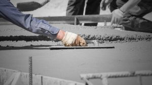 Concrete contractor using finishing trowel to level off concrete sidewalk