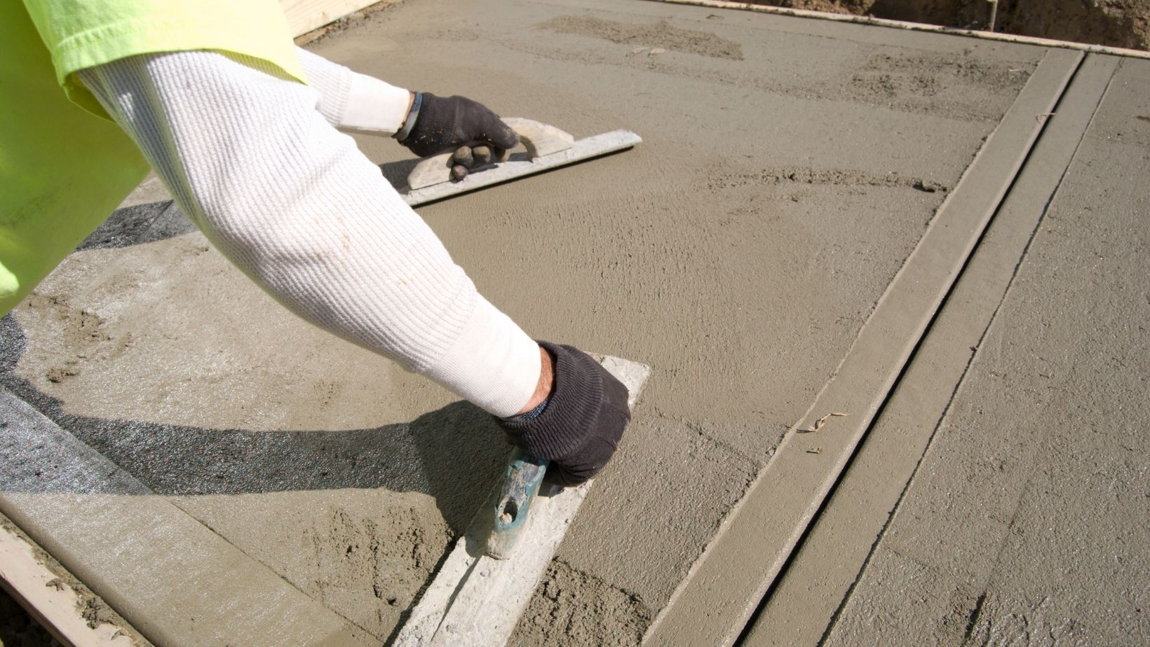 Contractor using finishing trowel to smooth out a new concrete sidewalk